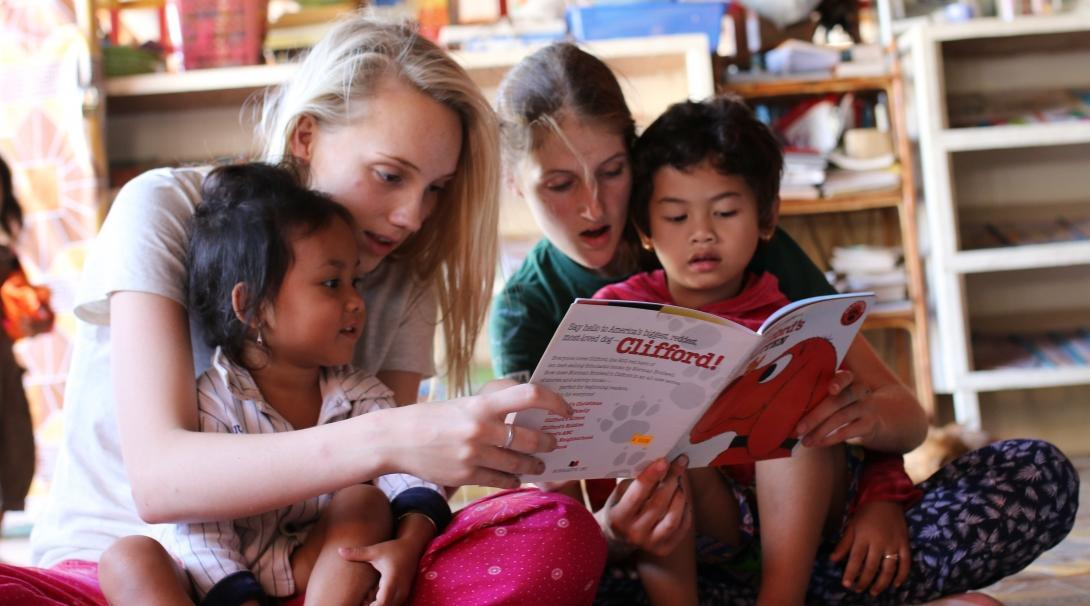 Children at a day care centre listen to a book being read by two female volunteers working with children in Cambodia.